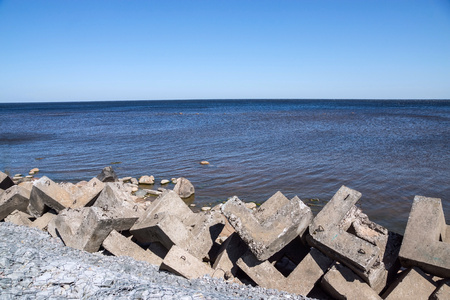 breakwaters: strengthening from concrete breakwaters on the bank of the sea gulf and the line of the horizon in a distance