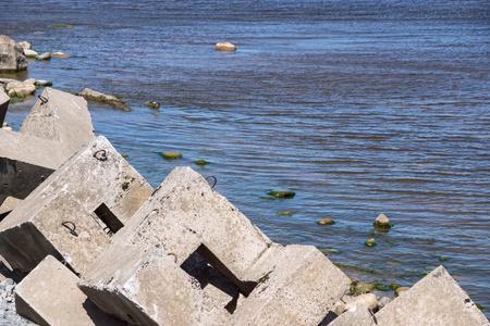 укрепление: укрепление бетонных волнорезов от на берегу моря в заливе крупным планом
