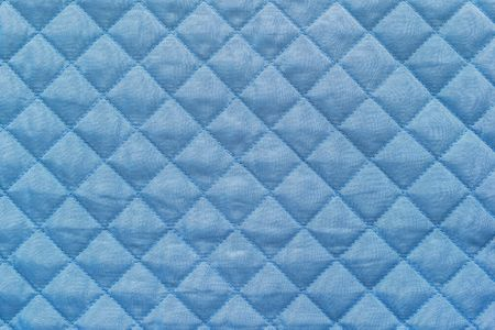quilted: blue quilted synthetic fabric with grained texture for empty and pure abstract backgrounds
