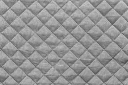 silvery quilted synthetic fabric with grained texture for empty and pure abstract backgrounds
