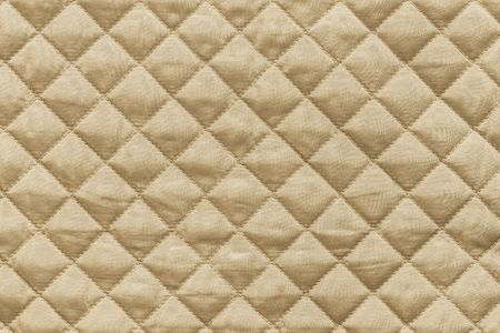 quilted: golden quilted synthetic fabric with grained texture for empty and pure abstract backgrounds Stock Photo
