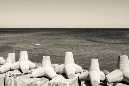 strengthening: strengthening from concrete breakwaters on the bank of the sea gulf and the line of the horizon in a distance in beige tones