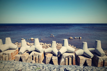 укрепление: strengthening from concrete breakwaters on the bank of the sea gulf and the line of the horizon in a distance in a retro tones