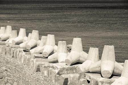 breakwaters: strengthening from concrete breakwaters on the bank of the sea gulf in beige tones