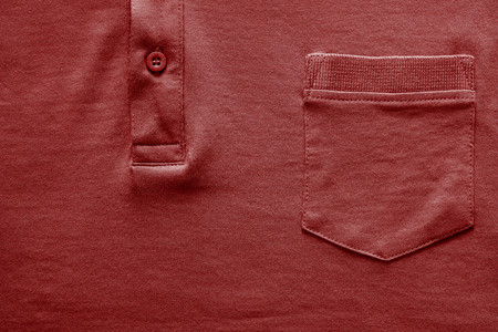red shirt: closeup part of a shirt from cotton fabric of red color with a big pocket and a fastener with the button Stock Photo
