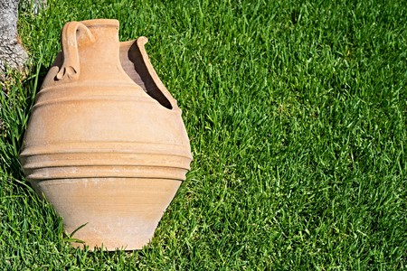 receptacle: one broken big ancient ceramic pot closeup against a grass of a lawn and a blank space for the text