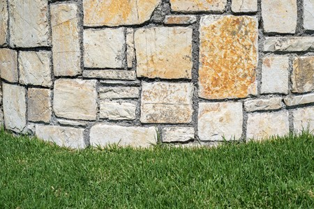 abstractions: part of a stone structure or brick wall from a natural stone on a lawn for abstractions and a blank space for the text