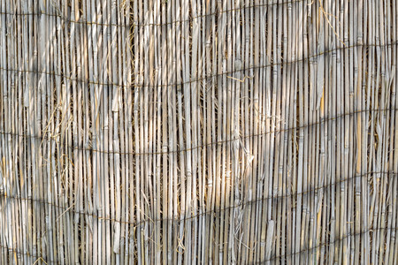partition: texture of an old reed or straw partition or curtain for empty and abstract backgrounds
