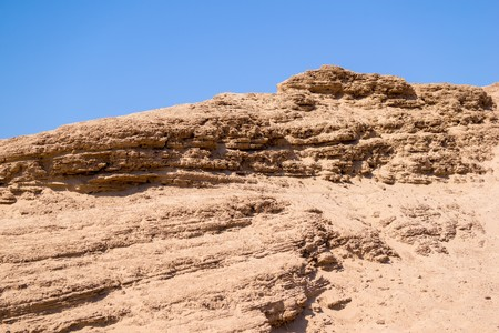 eminence: the big sandy hill or barkhan against the bright blue sky Stock Photo