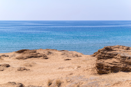 eminence: the sandy hill or barkhan against the horizon of the bright blue sky and the sea