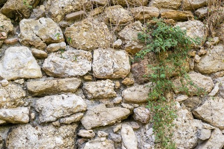 channeled: texture of an old stone wall of ancient fortress closeup for abstract backgrounds and for wallpaper