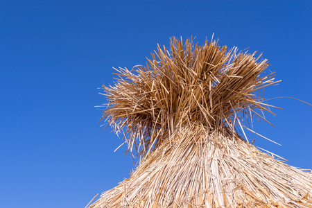 part of the textured hut roof from straw or a reed closeup against an empty and clear sky Stock Photo