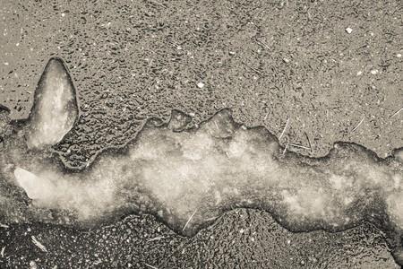 granizados: aguanieve o montón de nieve húmeda de una forma abstracta en una superficie de asfalto en tonos beige