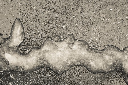 heap of snow: slush or heap of damp snow of an abstract form on an asphalt surface in beige tones