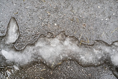 heap of snow: slush or heap of damp snow of an abstract form on an asphalt surface of natural dirty color