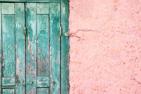 outworn: part or fragment of a wall and door of the old house in vintage style for the textured abstract architectural background and for wallpaper