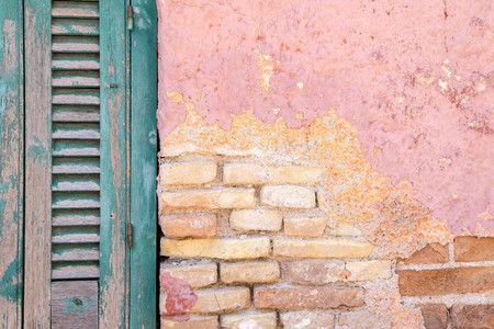 wiped out: part or fragment of a brick wall with the destroyed plaster and a window with a wooden shutter of the old house in vintage style Stock Photo