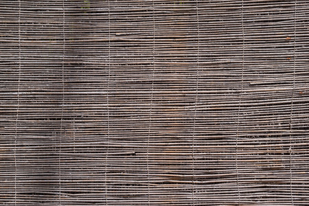 outworn: textured a curtain or a screen from a dry reed or straw for an abstract background and for wallpaper of natural color