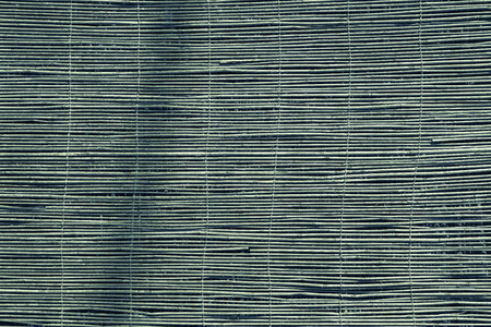 outworn: textured a curtain or a screen from a dry reed or straw for an abstract background and for wallpaper of green color