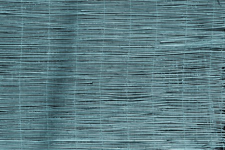 outworn: textured a curtain or a screen from a dry reed or straw for an abstract background and for wallpaper of blue color