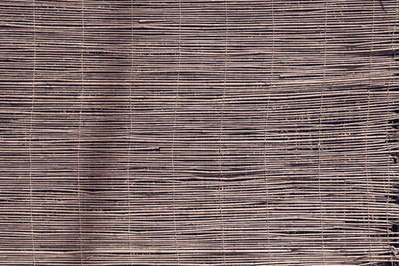 wiped out: textured a curtain or a screen from a dry reed or straw for an abstract background and for wallpaper of brown color Stock Photo