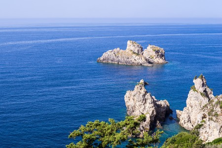 the crag: the gray stony crag in the blue sea or at the ocean for a natural background