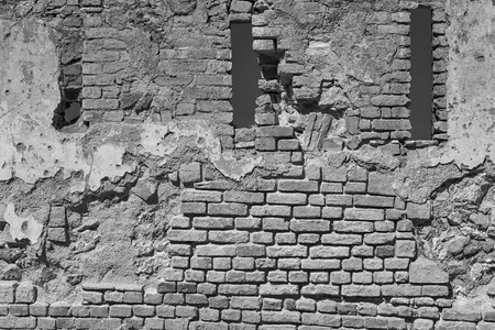 wall bricks: the old destroyed brick wall with loopholes of a fortress or the building for the textured vintage background