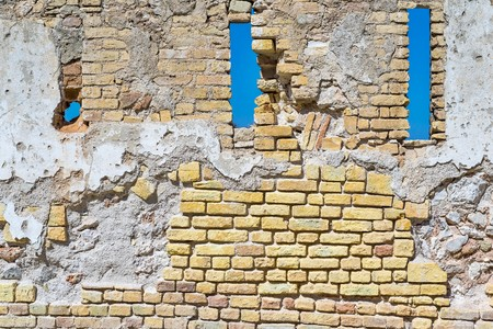 the old destroyed brick wall with loopholes of a fortress or the building for the textured vintage background