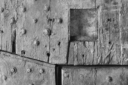 loophole: part old wooden riveted gate of fortress or a fragment of a door with a loophole for the textured abstract background and for wallpaper