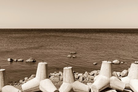 breakwaters: strengthening from concrete breakwaters on the bank of the sea gulf and the line of the horizon in a distance in sepia tones