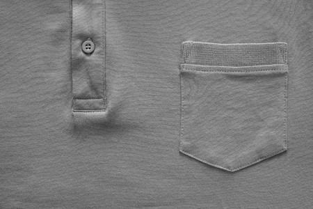 fastener: closeup part of a shirt from cotton fabric of gray color with a big pocket and a fastener with the button