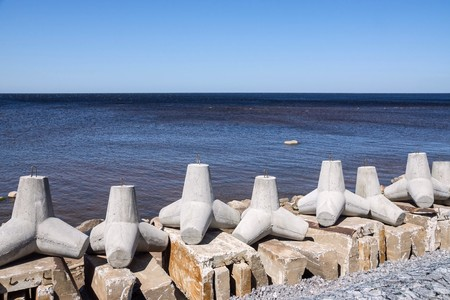 breakwaters: strengthening from big concrete breakwaters on the bank of the sea gulf and the line of the horizon in a distance Stock Photo