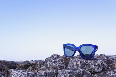 separately: modern sunglasses from blue plastic are located separately on a stone against the blue sky a closeup