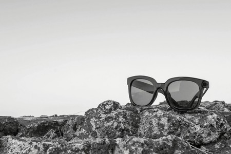 separately: modern sunglasses from plastic of monochrome color are separately on a stone closeup against the empty Stock Photo