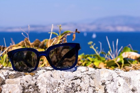 separately: modern sunglasses for sight are located separately on a stone against a landscape a closeup