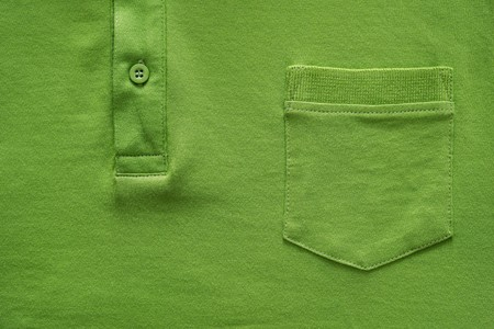 big shirt: closeup part of a shirt from cotton fabric of green color with a big pocket and a fastener with the button