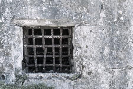 celosía de hierro viejo oxidado en un muro de piedra de la cárcel antigua o una mazmorra