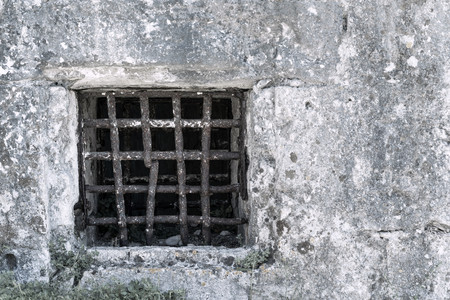 ancient prison: window lattice from old rusty iron on a stone wall of ancient prison or a dungeon Stock Photo
