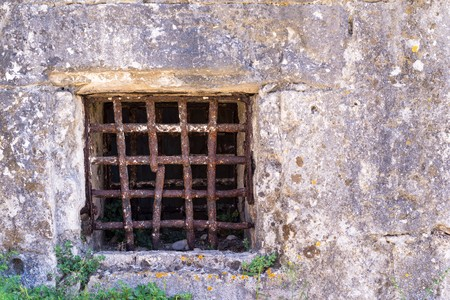ancient prison: window grating from old rusty iron on a stone wall of ancient prison or a dungeon