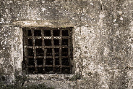 ancient prison: window grate from old rusty iron on a stone wall of ancient prison or a dungeon Stock Photo