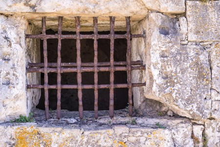 lattice window: window lattice from old rusty iron on a stone wall of ancient dungeon or a prison Stock Photo