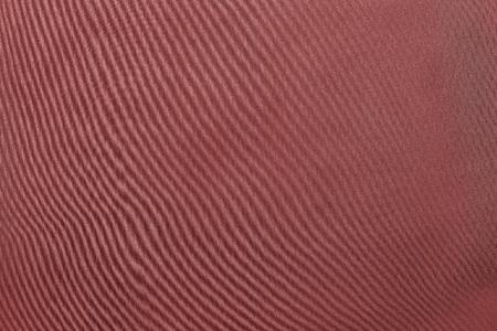 grained: the abstract textured background from textile material or from fabric of pale scarlet monochrome color with design grained of texture Stock Photo