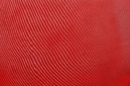 grained: the abstract textured background from textile material or from fabric of bright red monochrome color with design grained of texture