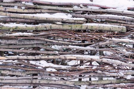 snowcovered: snow-covered wattle or fence from wooden branches for the natural textured background Stock Photo
