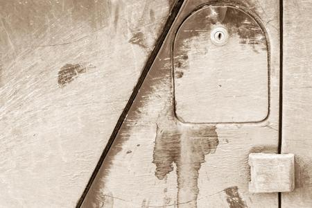 dirty car: cover of an automobile gasoline tank with the lock on a fragment of the old dirty car for an abstract industrial background of tone sepia