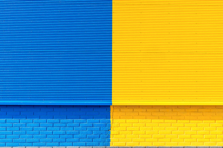 channeled: the textured background from corrugated iron and a brick of yellow and blue color and a blank space for the text