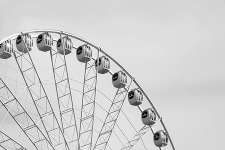 metal monochrome: metal design a ferris wheel or an attraction with cabins for a panoramic review against the sky of monochrome tone Stock Photo