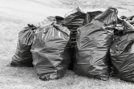 big black plastic bags are filled with garbage and located on open space for loading and export on utilization Stock Photo
