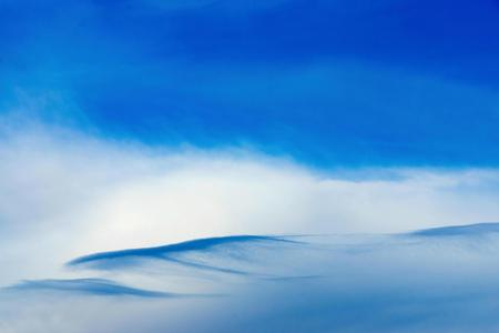 singly: the blue white cloudy sky with a separate cloud of an abstract form for a natural background