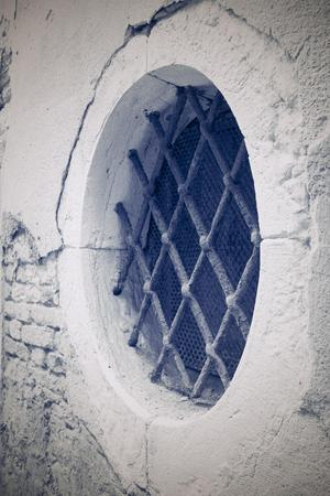 lattice window: old brick facade of the ancient building with a round window and a iron lattice in retro style